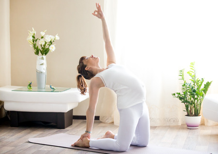 ushtrasana: Healthy Pregnancy Yoga and Fitness concept. Young pregnant yoga woman working out in living room. Pregnant model doing prenatal camel pose, ustrasana, yoga backbend exercise