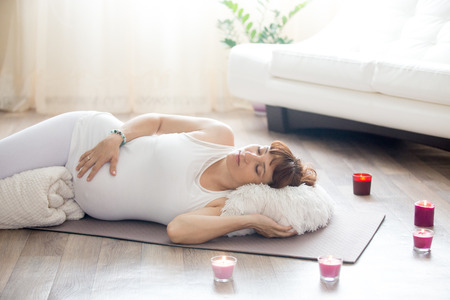 Healthy lifestyle concept. Pregnancy Yoga and Fitness. Young pregnant yoga woman resting after working out in living room interior. Pregnant model lying in prenatal Shavasana (Corpse, Dead Body Pose)