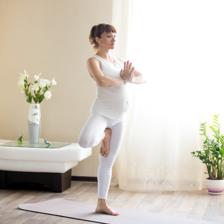 prenatal: Healthy Pregnancy Yoga and Fitness concept. Young pregnant yoga woman working out in living room. Pregnant model doing prenatal Tree posture, Vrksasana yoga pose with Namaste gesture Stock Photo