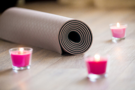 keep fit: Rose-colored lighted pink wax candle and rolled brown yoga, pilates mat on the floor ready for workout. Close up. Healthy life, keep fit concepts. Focus on mat