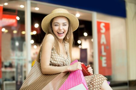 Portrait of cheerful young pretty woman wearing hat in shopping centre, hugging tightly bags with purchases, laughing happily squinted. Fashion, sale, shopping concept. Red sale sign on background 版權商用圖片