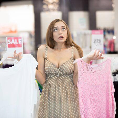Jonge mooie vrouw in kledingwinkel maken moeilijke beslissing op een verlies kiezen tussen twee jurken, niet in staat om te beslissen. Ze is schouders ophaalt opzoeken, die witte en roze jurken. vierkant schot Stockfoto