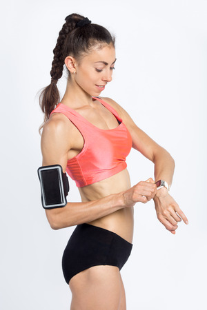 tummy time: Portrait of beautiful happy fitness person wearing armband with smartphone and red sportswear top looking at smartwatch at sport practice. Sporty girl working out and checking progress on smart watch