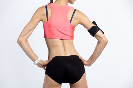Closeup of torso of beautiful young person wearing armband with smartphone, smartwatch, shorts and red sportswear top. Cool model girl with perfect butt, slim waist and hips working out. Back view