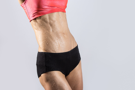 Attractive young bodybuilder person with ideal body wearing red sportswear bra and shorts sweating after working out. Sexy sporty model girl posing against grey background. Close-up of abs Stock Photo