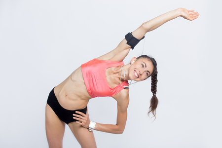 Portrait of beautiful happy young person wearing armband and black and red sportswear doing side bend exercises. Smiling sporty model girl working out, listening music, using smartwatch. Studio