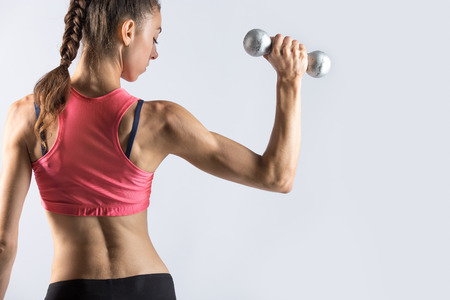 Attractive young fitness person wearing red sportswear top lifting dumbbells. Sporty model girl working out, doing weight training with dumbbells on grey background. Back view. Copy space