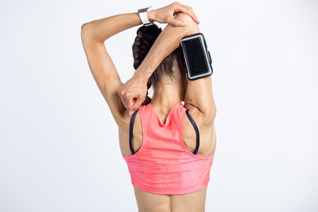 Closeup of torso of beautiful young person wearing armband with smartphone, smartwatch, shorts and red sportswear top. Cool model girl warming up, doing overhead triceps stretch exercise. Back view