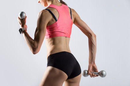 Attractive young fitness person wearing red sportswear top lifting dumbbells. Sporty model girl working out, doing weight training with dumbbells on grey background. Rear view. Closeup