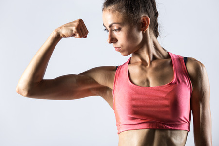 Attractive young fitness person with perfect body wearing red sportswear bra posing standing against grey background. Serious sporty model girl looking at biceps muscles. Close-up portrait