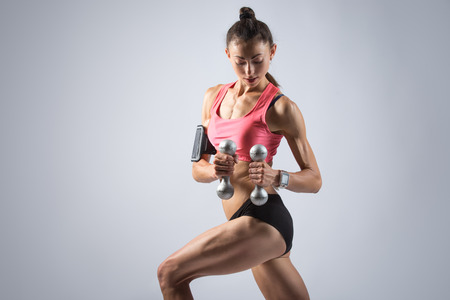 lunge: Portrait of beautiful young fit person wearing smartwatch, smartphone armband and red sportswear top holding dumbbells. Sporty model working out, doing weight training with dumbbells in lunge position
