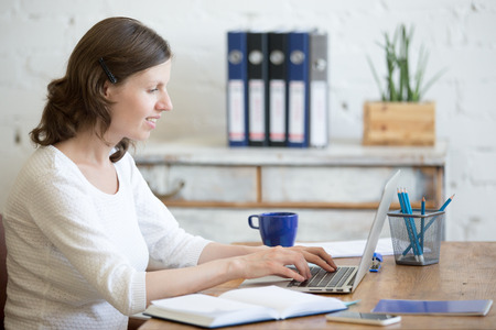 Portrait of young business woman using laptop in home office interior in loft space. Happy casual office person sitting with laptop in modern office workplace, typing, looking at screen smiling Stock Photo