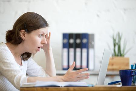 Jonge beklemtoonde zakenvrouw zitten met laptop en wat betreft hoofd met geschokte gelaatsuitdrukking. Verrast zakelijke persoon te kijken naar laptop computer bezorgd en verbaasd met open mond en grote ogen Stockfoto