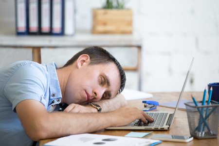 Portrait of young man lying on the table in front of laptop, sleepy, tired, overworked or lazy to work. Attractive business man napping in his home office relaxing after work on laptop computer