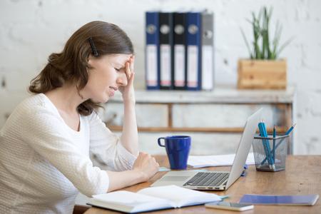 Jonge beklemtoonde zakenvrouw zitten in de voorkant van de laptop en ontroerende hoofd met pijnlijke uitdrukking. Bedrijfs persoon voelt pijn, lijden aan migraine na het werken op de pc, overwerkt of depressief Stockfoto