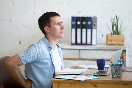 Young stressed businessman sitting in front of laptop and holding his waist with pained expression. Business man feeling pain, touching his aching back, suffering from backache after working on pc