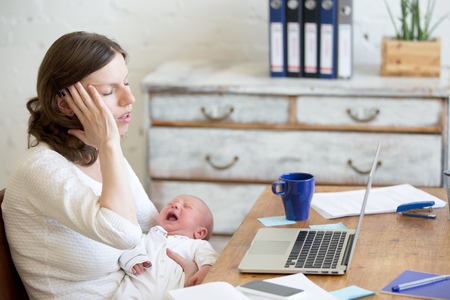 Young businesswoman holding newborn crying babe while sitting with laptop and touching head with pained expression. Career mom suffering from migraine after working on pc and nursing crying child