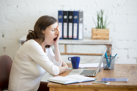 Portrait of young woman sitting at table in front of laptop, sleepy, tired, overworked, lazy to work. Attractive business woman yawning in home office relaxing or bored after work on laptop computer Stock Photo
