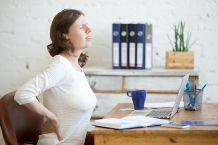 Young destacó mujer de negocios sentado delante del ordenador portátil y la celebración de su cintura con expresión de dolor. Mujer de negocios que sienta dolor, dolor de espalda tocando, sufriendo de dolor de espalda después de trabajar en el PC