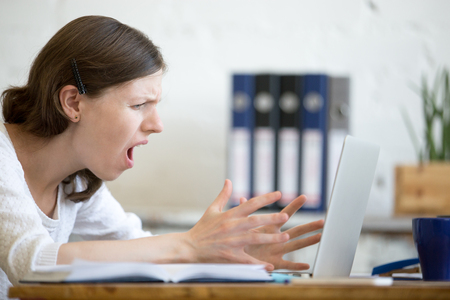Young stressed businesswoman sitting with laptop and screaming with angry expression. Furious business person feeling irritated while using pc, gesticulating and yelling. Negative human emotion