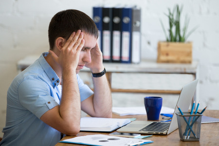 Young stressed businessman sitting in front of laptop and touching his head with pained expression. Business man feeling pain, suffering from migraine after working on pc, overworked or depressed