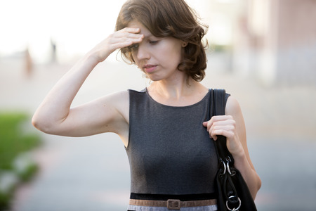 Portrait of young office woman walking on the street in summer, frowning, holding her head with hand, businesswoman has forgotten something or feeling ill, dizzy, tired