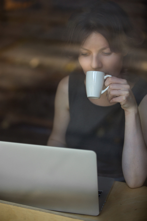 interior shot: Portrait of beautiful young woman sitting in modern cafe holding cup of drink, sipping coffee, working on laptop, looking at the screen, interior shot through window glass Stock Photo