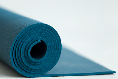 Rolled up blue yoga, pilates or fitness mat on the floor, copy space, close up