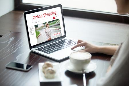 Junge Frau im Kaffee mit einer Tasse Kaffee sitzen und Kuchen, auf Laptop-Computer, Online-Shopping-Web-Service. Attraktive weibliche Browsing-Shopping-Website. Nahaufnahme Blick über die Schulter Standard-Bild - 63556228