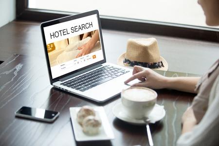 hospedaje: Mujer joven atractiva que se sienta en café con la taza de café y pasteles, trabajando en equipo portátil, en busca de alojamiento utilizando servicios web en línea, la reserva de un hotel en la página web. Vista sobre el hombro