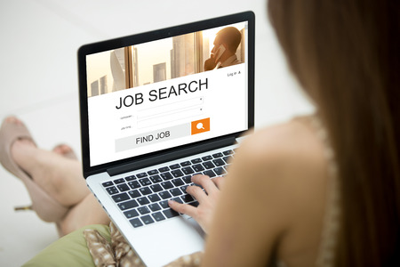 looking for job: Casual young woman sitting on sofa with notebook, working on laptop computer, searching for job using online web service. Attractive female looking for job on website. HR, recruitment, career concept