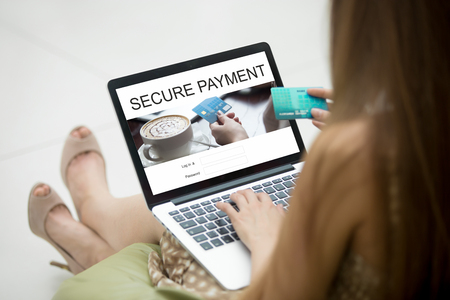 over paying: Casual young woman sitting on sofa with notebook, working on laptop computer, using secure payment software for online payments, paying for online shopping on laptop. Closeup view over the shoulder Stock Photo