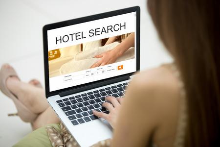 hospedaje: Casual joven sentado en el sofá con el portátil, trabajando en equipo portátil, en busca de alojamiento utilizando servicios web en línea, la reserva de un hotel en la página web. Primer punto de vista sobre el hombro