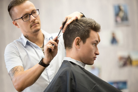 interior shot: Interior shot of working process in modern barbershop. Side view portrait of attractive young man getting trendy haircut. Male hairdresser serving client, making haircut using metal scissors and comb