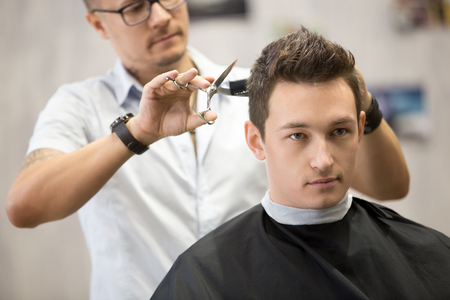 Interior shot of working process in modern barbershop. Close-up portrait of attractive young man getting trendy haircut. Male hairdresser serving client, making haircut using metal scissors and comb Stock Photo