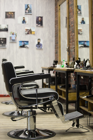 male grooming: Row of black leather chairs in modern barber shop interior. Vertical indoors image