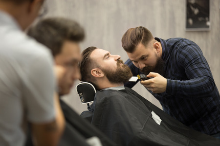 interior shot: Interior shot of working process in barbershop. Side view of handsome young man getting trendy beard haircut in modern barbershop. Cool male hairstylists serving clients