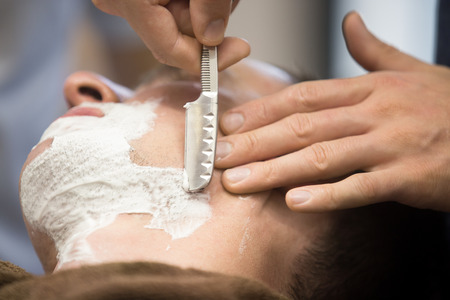 straight man: Interior shot of working process in modern barbershop. Close-up portrait of handsome young man getting beard shaving with straight razor. Focus on the blade