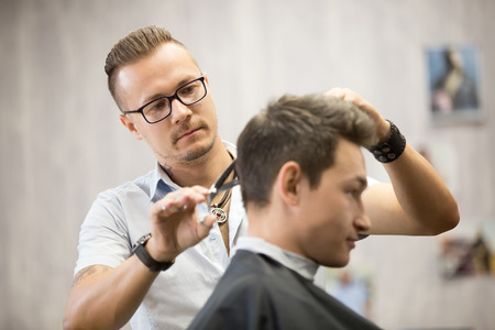 Working process in modern barbershop. Male hairdresser serving client, making haircut using metal scissors. Side view of attractive young man getting trendy haircut. Focus on hairstylist