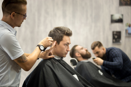 Interior shot of working process in barbershop. Side view of handsome young men getting trendy haircuts in modern barbershop. Cool male hairstylists serving clients Stock Photo