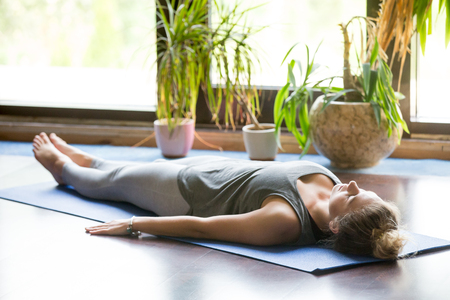 body posture: Attractive young woman working out at home, doing yoga exercise on blue mat, lying in Shavasana Corpse or Dead Body Posture , resting after practice, meditating, breathing. Full length