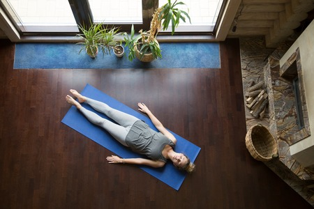 body posture: Attractive young woman working out in living room, doing yoga exercise on blue mat, lying in Shavasana Corpse, Dead Body Posture , resting after practice, meditating, breathing. Full length, top view Stock Photo