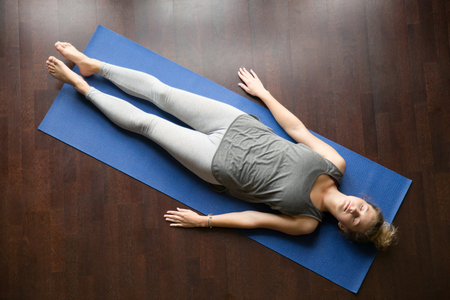 Attractive young woman working out at home, doing yoga exercise on blue mat, lying in Shavasana Corpse or Dead Body Pose , resting after practice, meditating, breathing. Full length, view from above