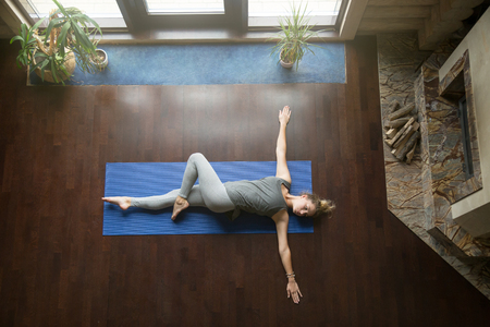Attractive young woman working out in living room, doing yoga exercise on wooden floor, lying in Reclining Spinal Twist, Jathara Parivartanasana, resting after practice, full length, top view
