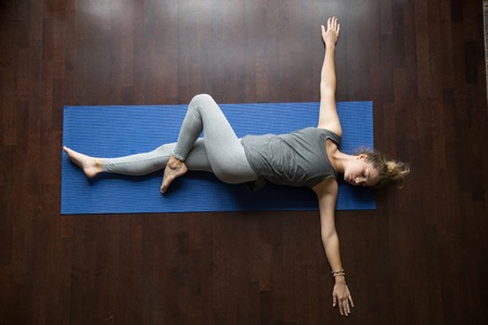 Attractive young woman working out indoors, doing yoga exercise on wooden floor, lying in Reclining Spinal Twist, Jathara Parivartanasana, resting after practice, full length, top view Standard-Bild