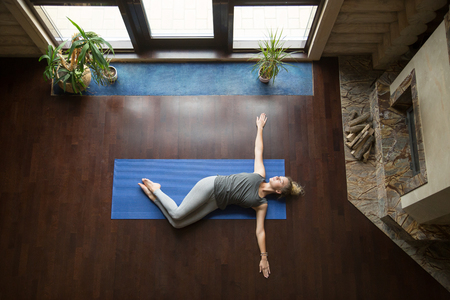 Attractive young woman working out in living room, doing yoga exercise on wooden floor, lying in Belly Twist Pose, Jathara Parivartanasana, resting after practice, full length, top view Reklamní fotografie - 63555754