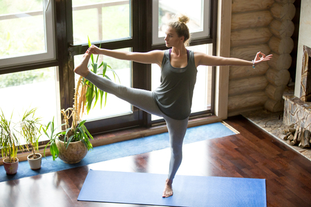 big toe: Full length portrait of attractive young woman working out at home in living room, doing yoga or pilates exercise on blue mat, standing in Utthita Hasta Padangustasana, Extended Hand to Big Toe pose Stock Photo