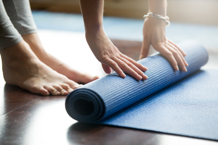 Close-up of attractive young woman folding blue yoga or fitness mat after working out at home in living room. Healthy life, keep fit concepts. Horizontal shot Stockfoto