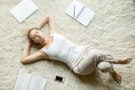 Beautiful young woman holding hands behind head while lying on white carpet on the floor in living room and sleeping after working on laptop or studying at home. Top view full length image Stock Photo