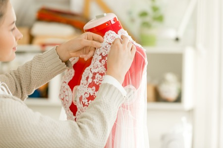 needle laces: Woman dressing a tailor dummy mannequin in a lace cloth. Concept photo, over a shoulder